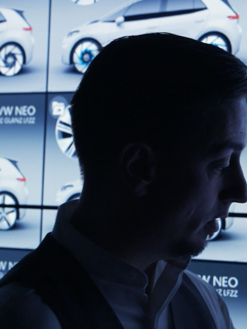 Volkswagen's Klaus Bischoff standing front of a video wall showing the ID.3