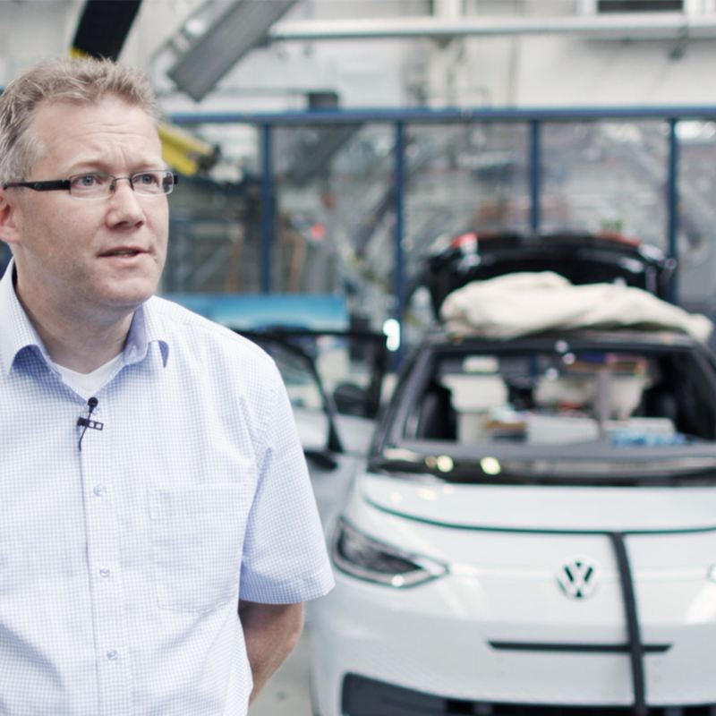 Volkswagen's Sven Köhler standing in front of an ID.3 on the production line