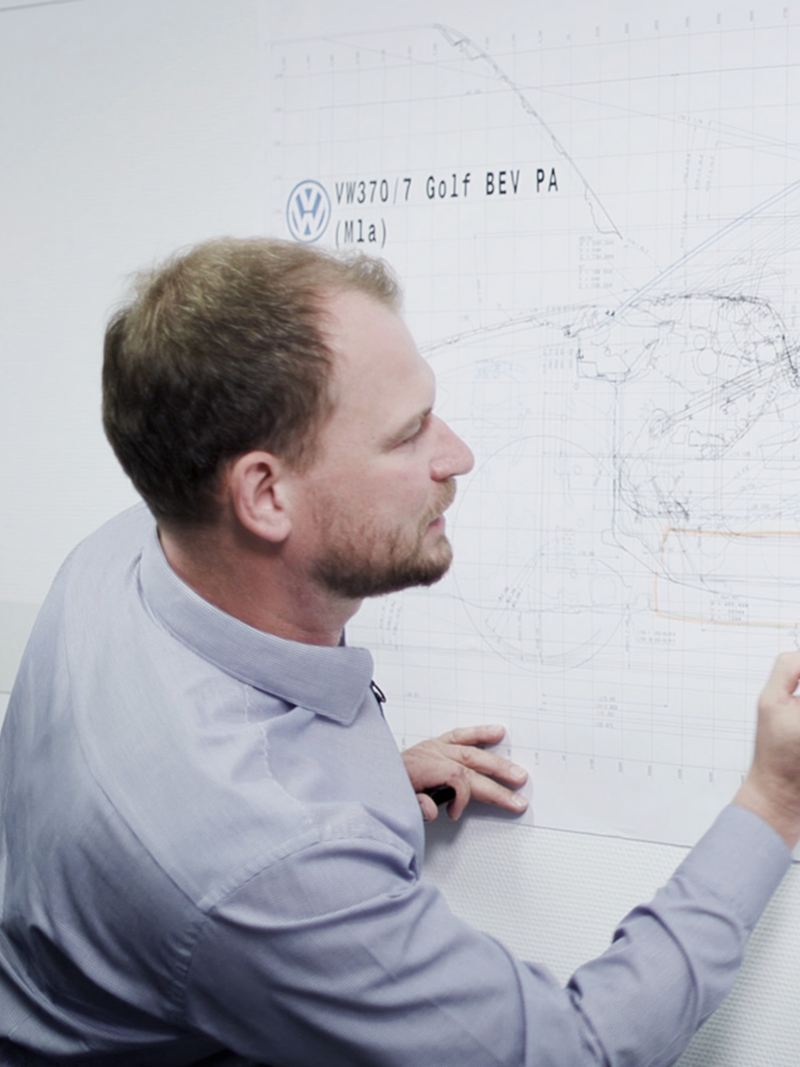 A Volkswagen engineer drawing on a whiteboard