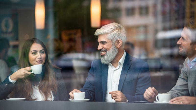 Eine Frau und zwei Männer tauschen sich in einem Café aus