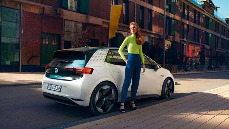 Auto eléctrico ID.3 de Volkswagen estacionado y chica parada a su costado