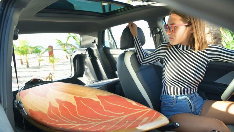 Mujer dentro de T-Cross acomodando tabla de surf en interior espacioso del SUV