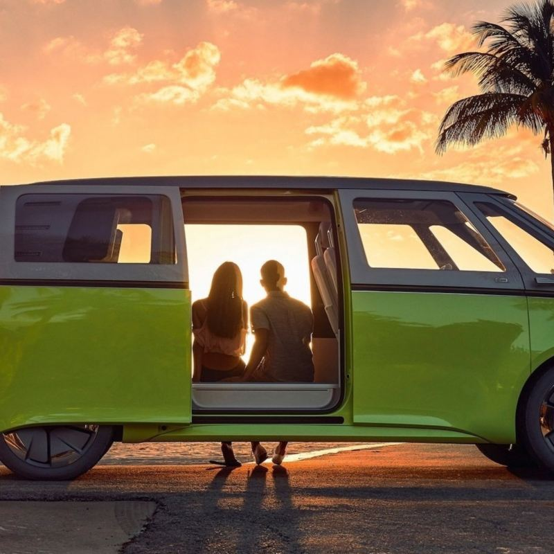Pareja sentada dentro de Combi eléctrica de Volkswagen estacionada en la playa