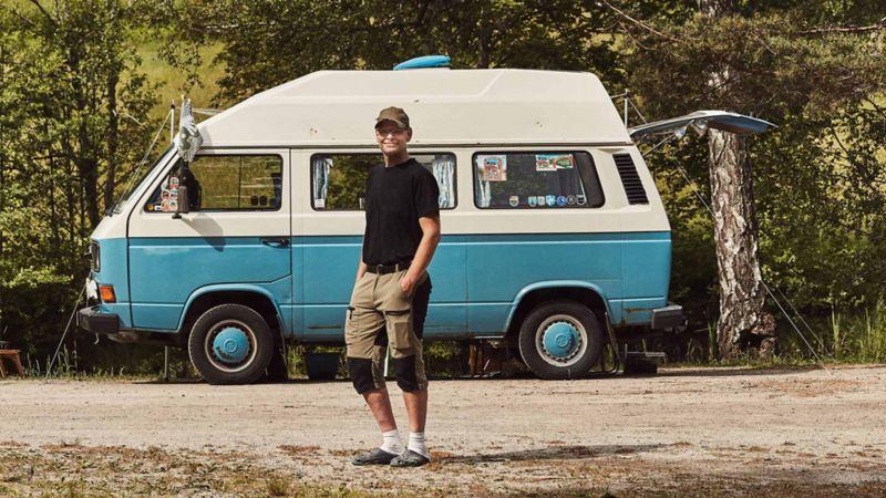 man står vid sin blåa VW folkasbuss campingbil