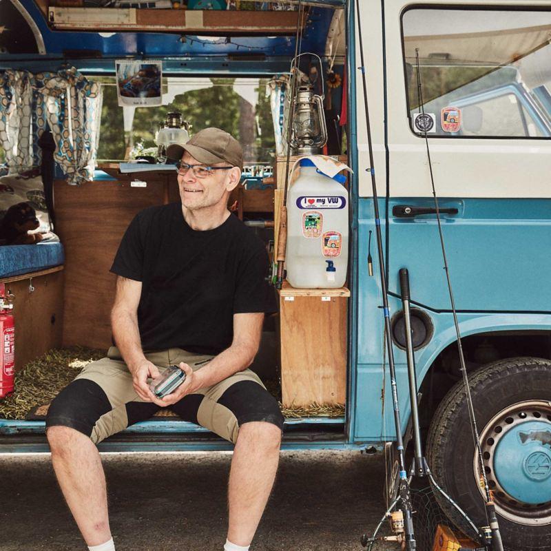 man sitter vid sin blåa VW folkasbuss campingbil