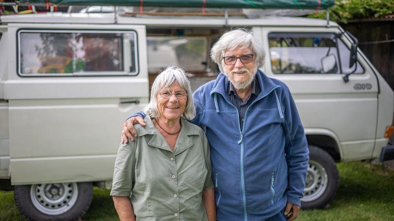 Ein älteres Paar steht vor einem VW Bus T3 Syncro.