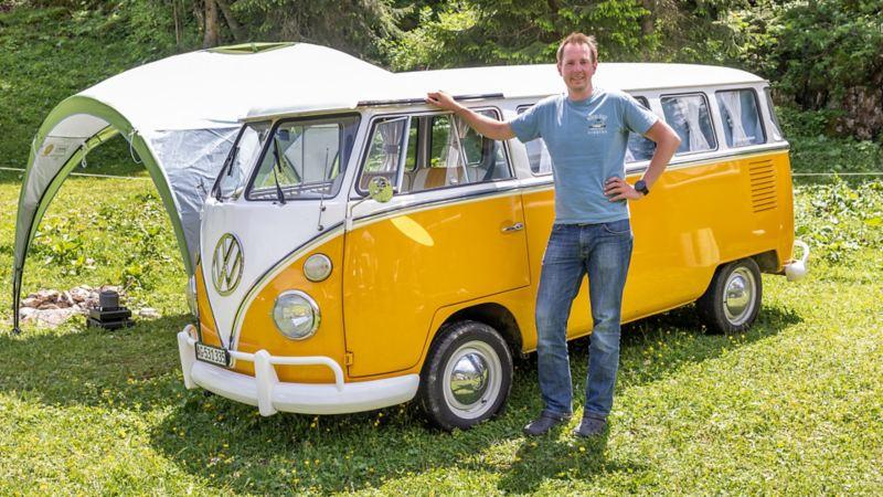 Jan steht vor einem gelben VW Bus T1.