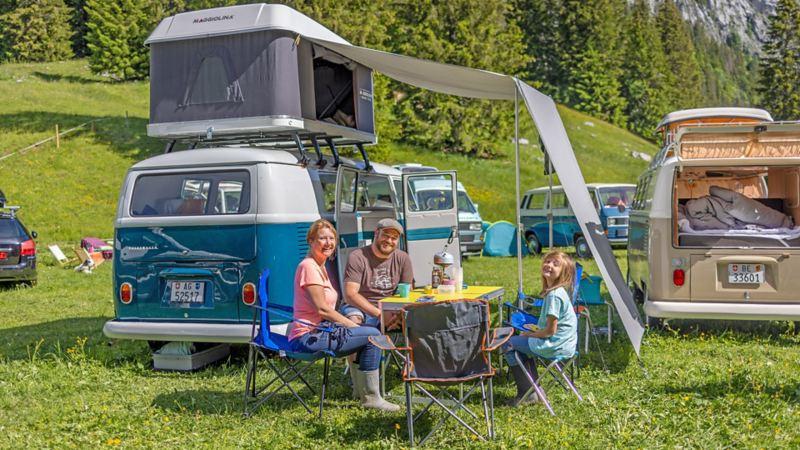 Eine Familie sitzt vor ihrem VW Bus T1.