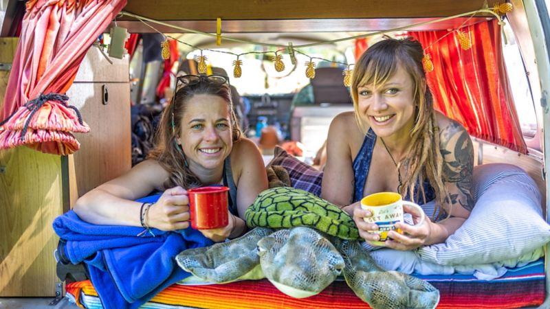 Zwei Frauen liegen in einem VW Bus T2a und halten Becher in der Hand.