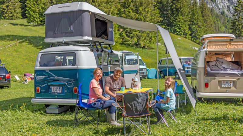 blauer Bulli parkiert auf der Wiese und eine Familie sitzt mit dem Campingtisch davor