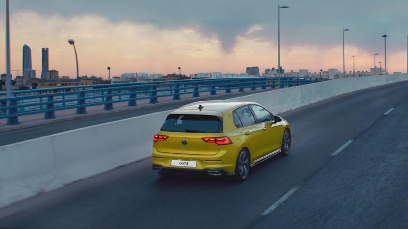 A yellow Volkswagen Golf 8 driving on an overpass
