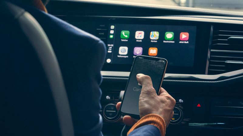 Man linking smartphone to VW van with App-Connect