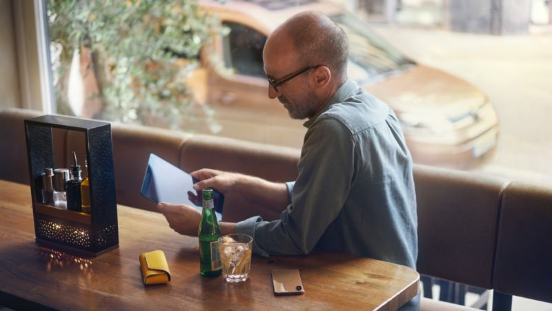 person sitting at a table using a tablet device