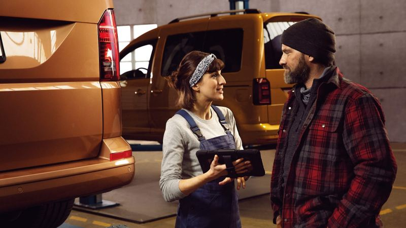VW technician discussing servicing with a customer.