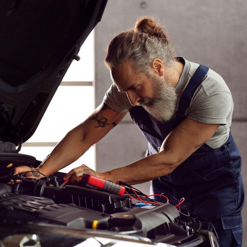 VW technician working on a van battery