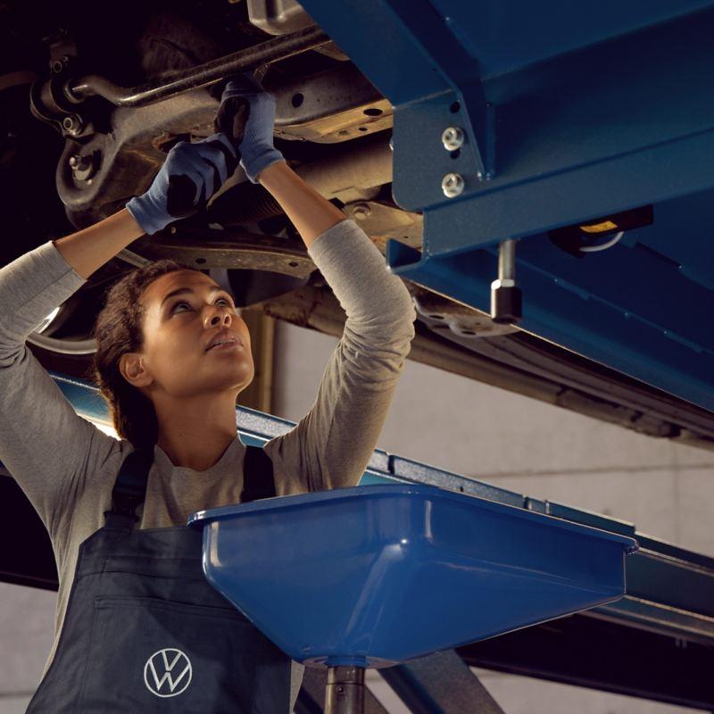 VW technician working on a vehicle underside