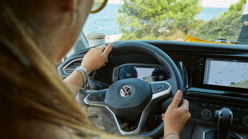 Eine Frau sitzt am Steuer und bedient die digitalen Dieste ihres Volkswagen Nutzfahrzeuges.