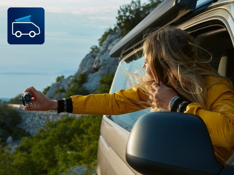 Eine Frau fotografiert die schöne Aussicht aus einem Volkswagen Nutzfahrzeuge California 6.1.