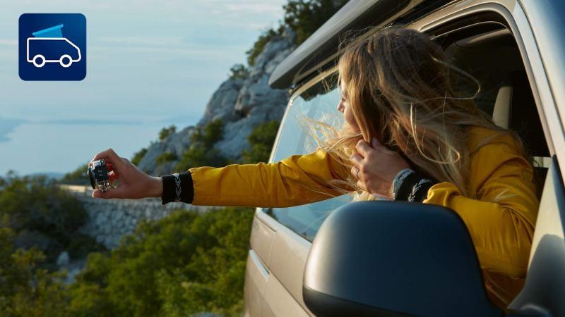 En kvinde fotograferer havet ud ad vinduet på en parkeret VW California 6.1. Ikonet for Cali-on-Tour-appen ses øverst til venstre på billedet.