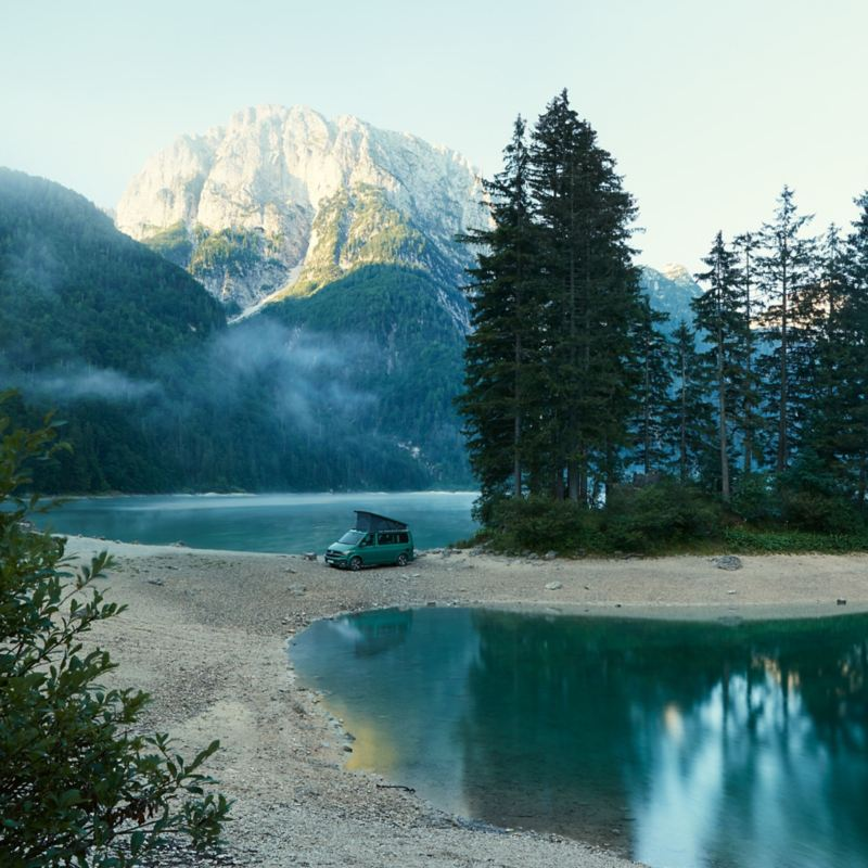 Ein Volkswagen California steht an einem See.