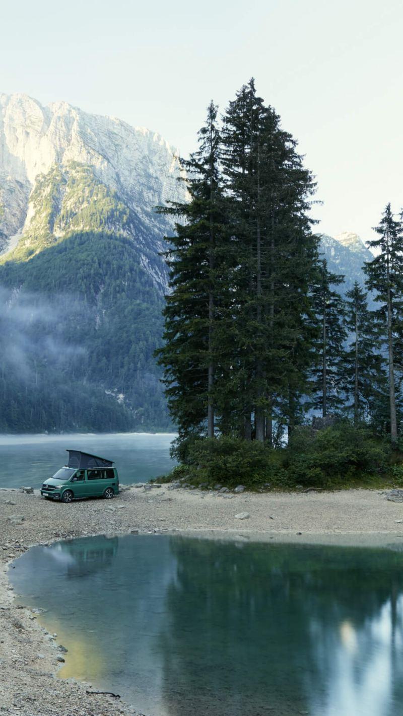 Ein VW California steht an einem See.