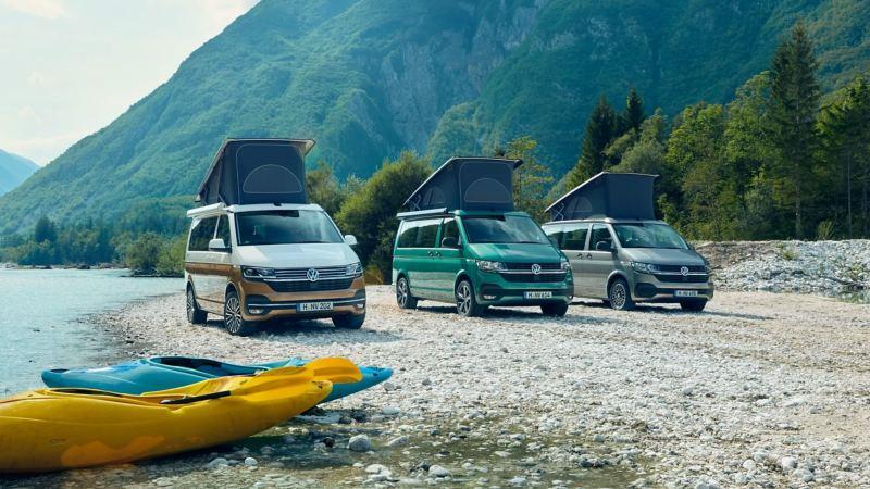 Drei VW California 6.1 Modelle stehen nebeneinander an einem Flussufer.