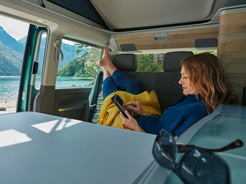 Eine Frau sitz in einem Volkswagen California und stöbert im Online-Shop.