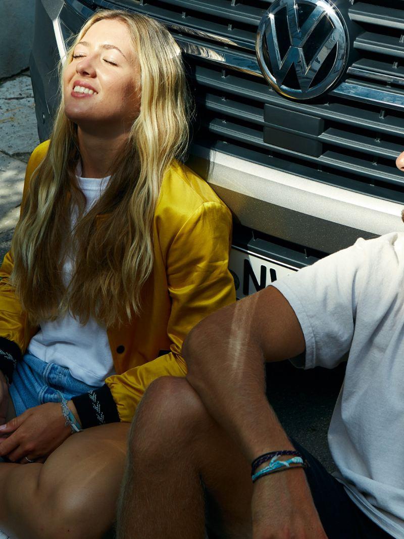 Eine Frau und ein Mann sitzen vor einem Volkswagen und entspannen in der Sonne.