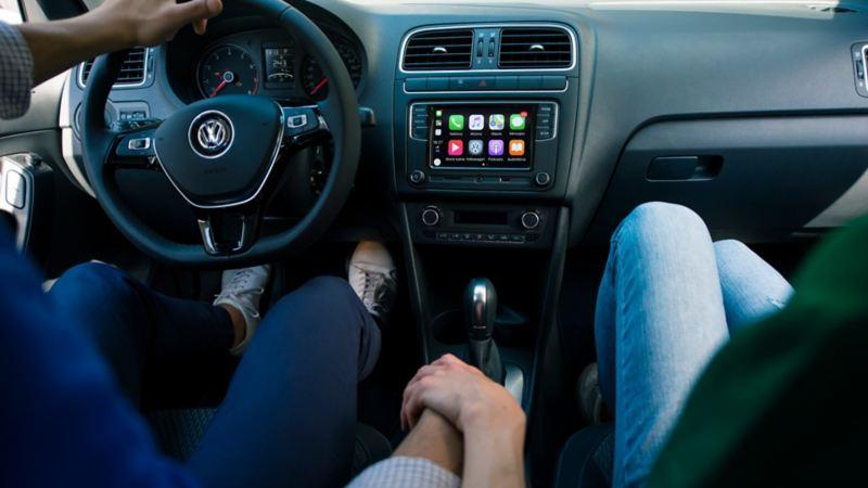 Pareja en cabina de automóvil Volkswagen con tablero y señalamientos detrás del volante