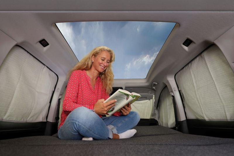 Kobieta we wnętrzu Caddy California, widok na panoramiczny dach