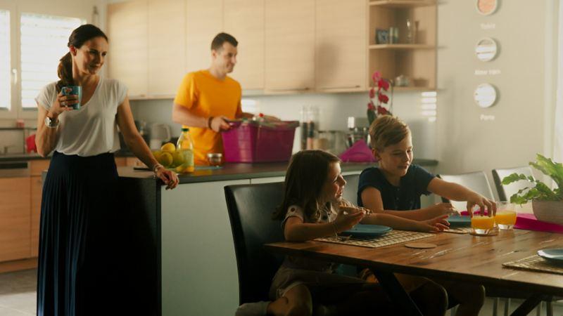 Deux enfants prennent leur petit-déjeuner pendant que les parents se préparent pour la vie quotidienne.