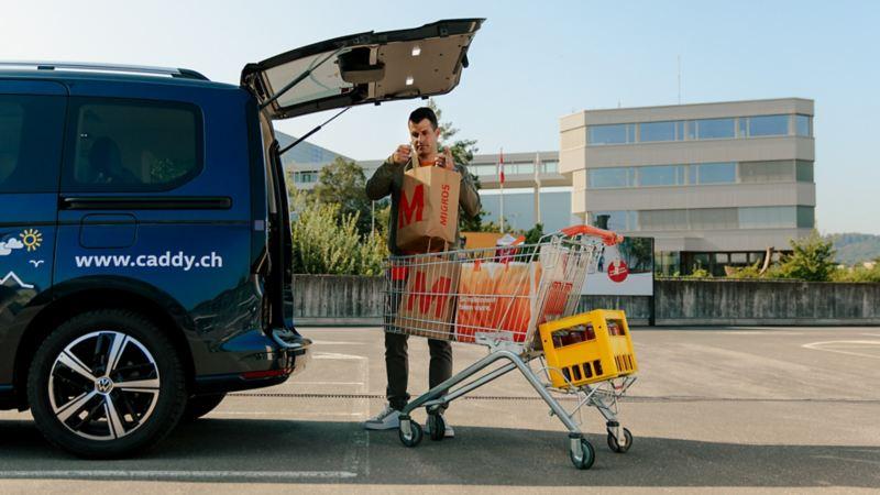 Un homme charge un caddy de provisions.