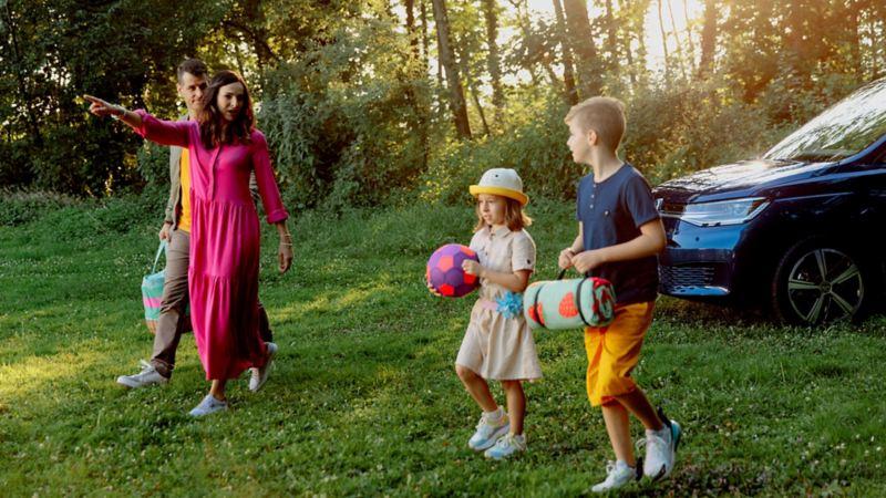 Une famille marche devant le Caddy