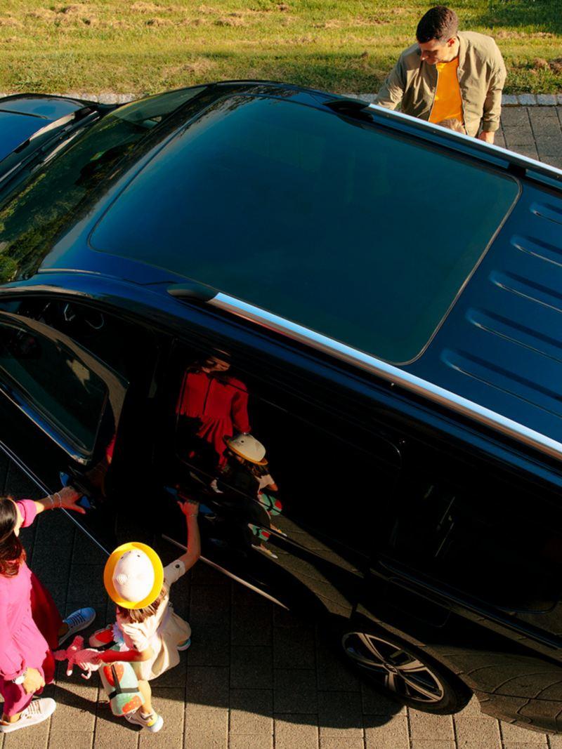 Une famille monte dans le Caddy, le tout est visible depuis une vue d'ensemble.