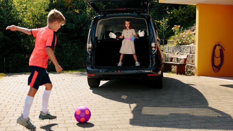 Deux enfants jouent au football en utilisant le coffre du Caddy comme but.