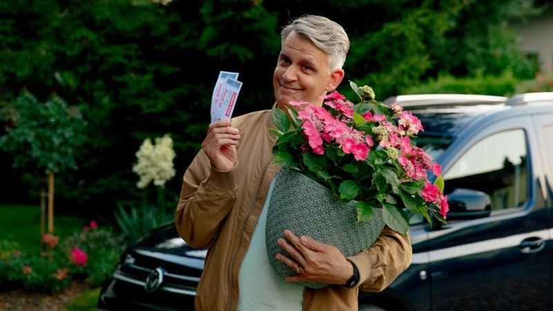 Un uomo tiene un vaso di fiori in una mano e due banconote nell'altra.