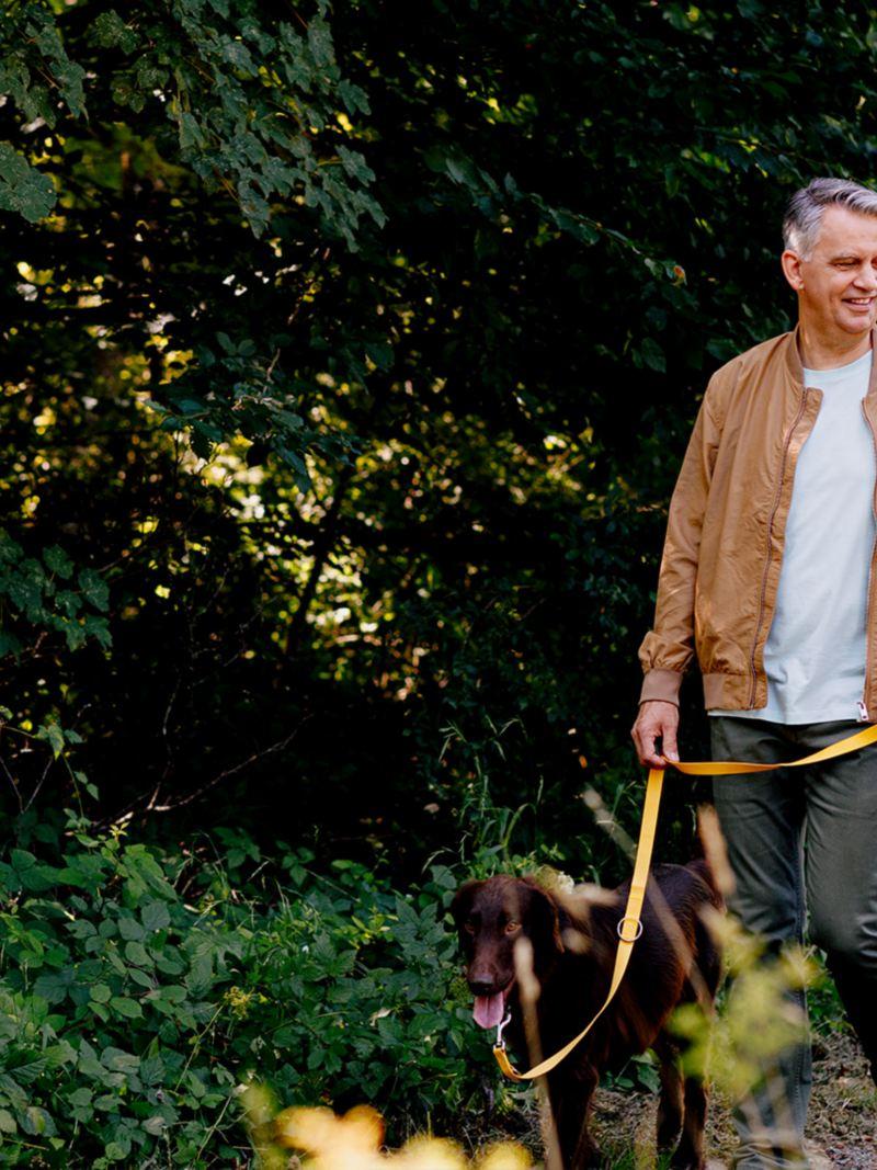 Una coppia che cammina con il suo cane nella natura