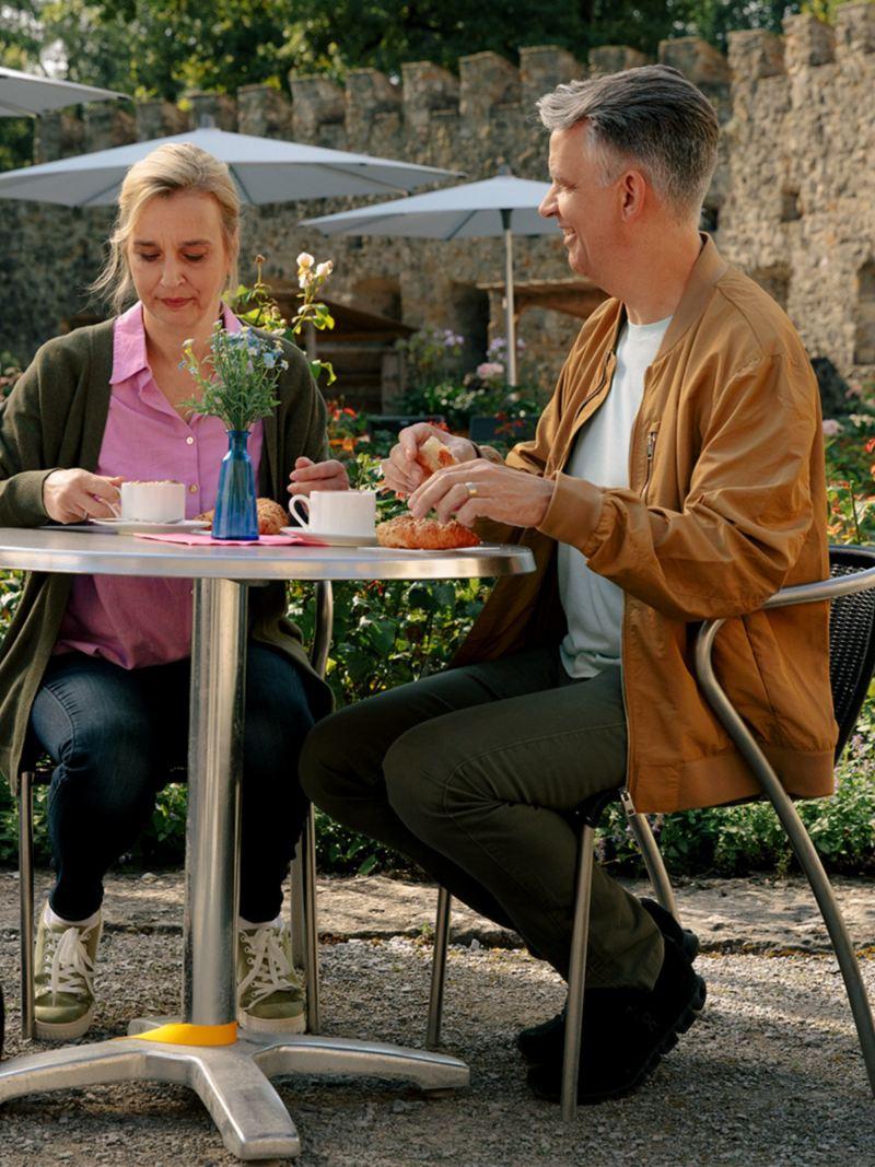 Su un tavolino da giardino, una coppia sta bevendo un caffè e un cane è sdraiato a terra accanto a loro.