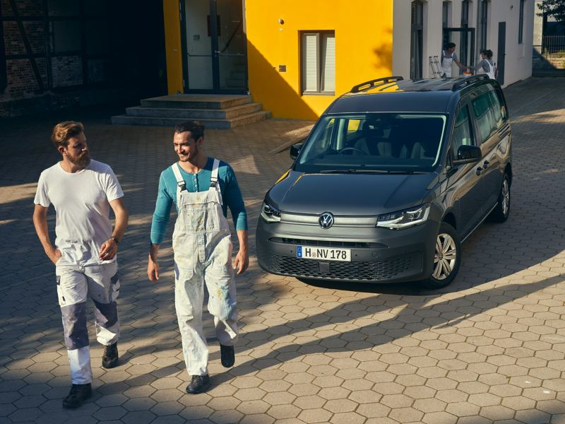 Two tradesmen walking away from parked Volkswagen Caddy Cargo Crewvan.