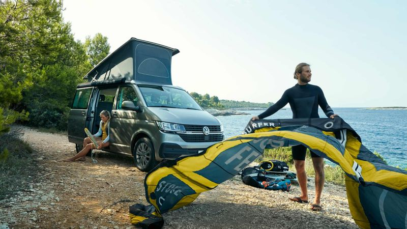 Person flaking kite surf in front of parked Volkswagen California with rooftop tent up.