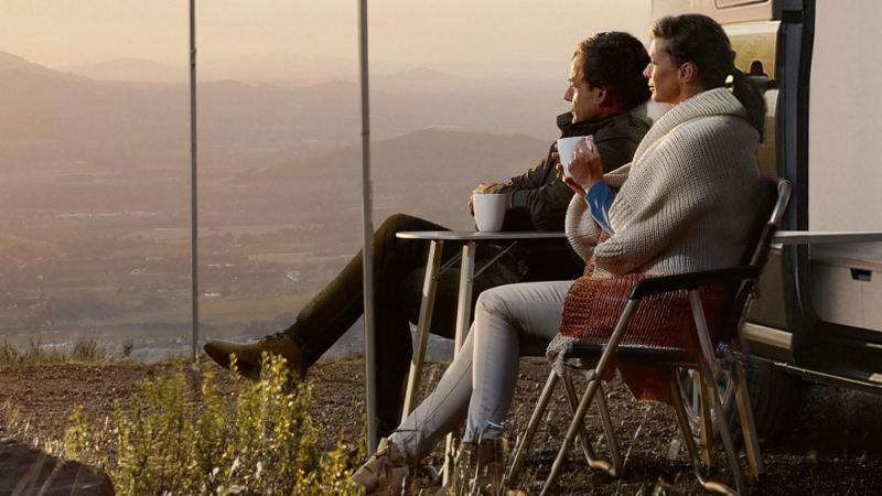 Un uomo e una donna seduti guardano un panorama di montagna mentre bevono un caffè.
