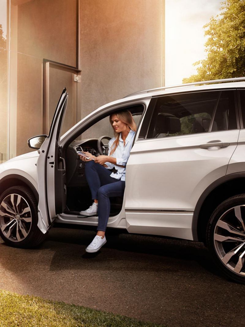 Women sitting in the VW Tiguan with her smartphone