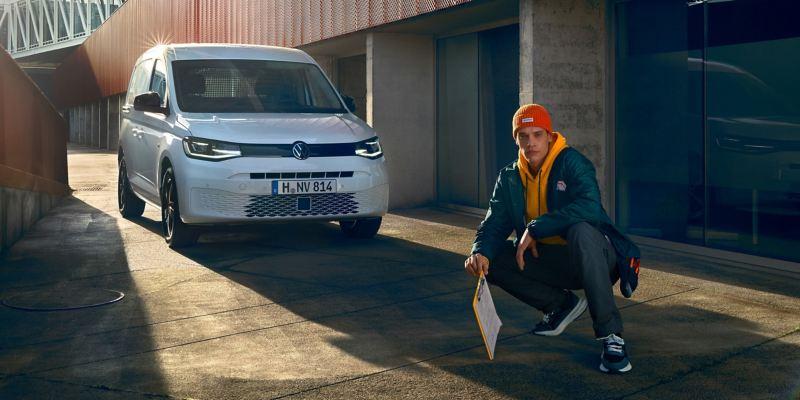 Un ragazzo semi seduto di fronte a Nuovo Caddy Cargo Volkswagen.