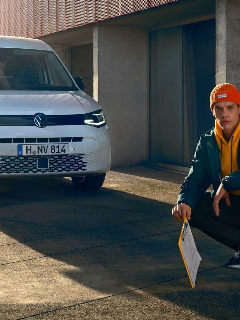 Le nouveau Volkswagen Caddy Cargo devant un complexe de bureaux moderne.