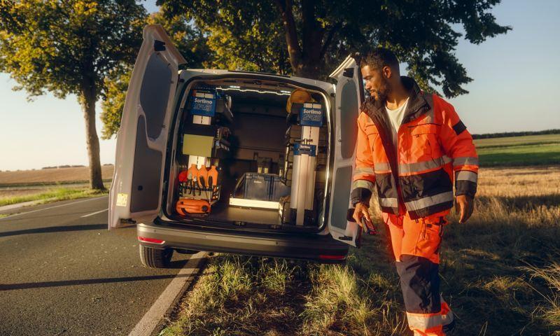 Bildet viser en sølvgrå Volkswagen Caddy Cargo liten varebil som står parkert i grøten langs en landevei og en arbeider som går mot varerommet som har en sortimo bilinnredning