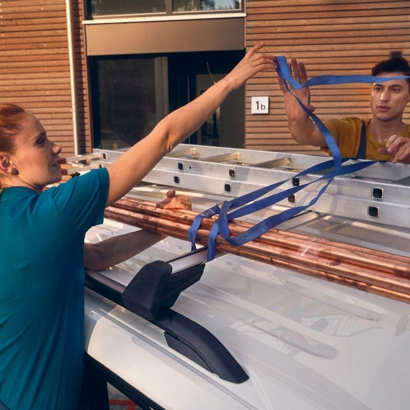 Zwei Handwerker verzurren eine Leiter auf einem VW Caddy.