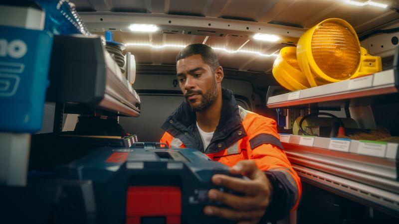 Bildet viser en Volkswagen Caddy Cargo liten varebil og en arbeider som står inne i varerommet og forsøker å finne frem til utstyr i sin bilinnredningsreol fra Sortimo