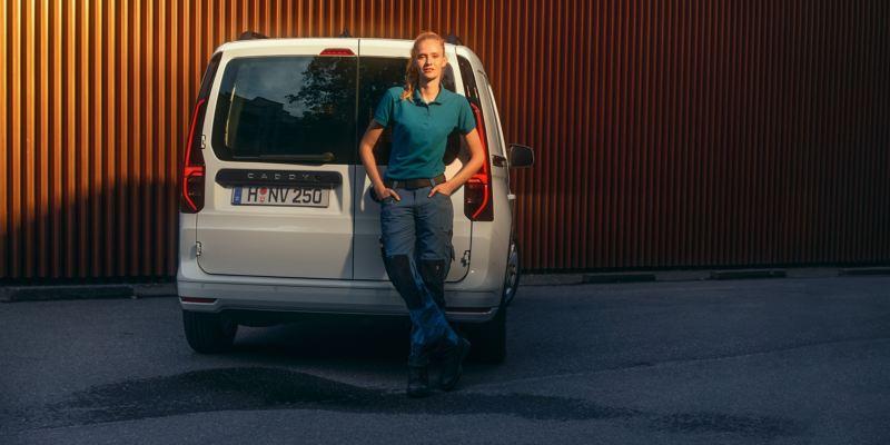 Uma mulher encostada às portas traseiras de abertura lateral da carrinha VW Caddy Cargo.