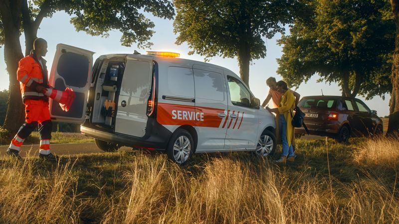 Un véhicule de service Volkswagen est sur le bord de la route et prête assistance.