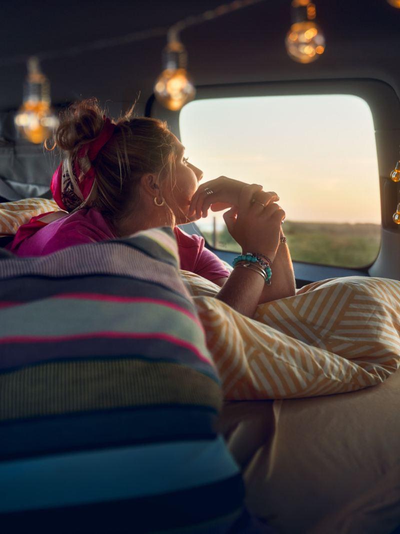Bildet viser soveplassen inne i Volkswagen Caddy California Maxi mini camper og en jente som ligger i sengen og kikker ut av vinduet på solnedgangen